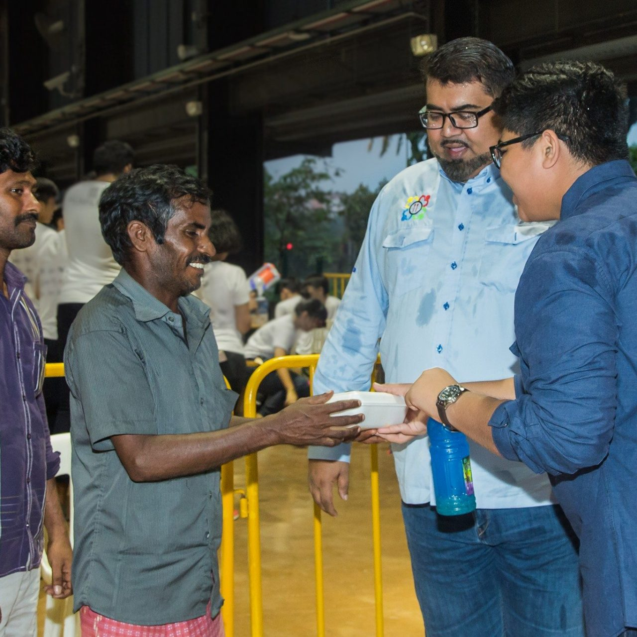 Nizar, second from right, helping to distribute food to foreign workers.