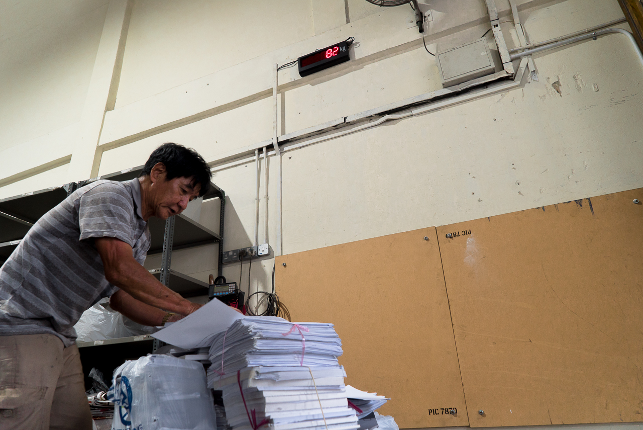 Mr Tan weighing his A4 paper, which can fetch him a higher price than cardboard.